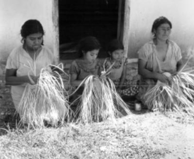 Mujeres y niñas hacen artesanias de palma