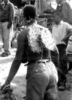 Hombre con nopales en la espalda y corona de espinas transita sobre una calle