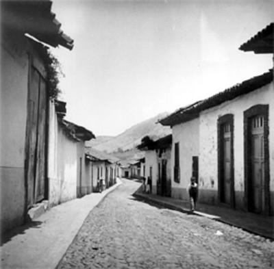 Gente camina por una calle empedrada