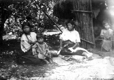 """Mujeres y niños sentados afuera de una choza, """"105. Grupa (sic) de indians"""""""