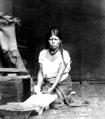 Mujer muele en metate