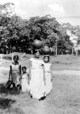 Mujeres cargan ollas en la cabeza