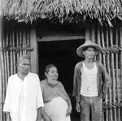 Hombres y mujer en la entrada de una choza
