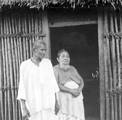 Mujer y hombre afuera de una choza