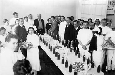 El médico Enrique Hernández Alvarez entre personal médico en un banquete, retrato
