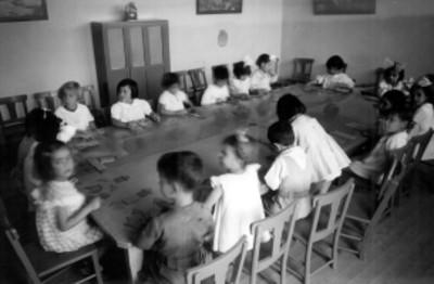 Niños y niñas jugando con figuras en un salón, retrato