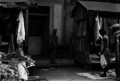 """Hombre con bastón junto a puestos de ropa en el mercado de """"La Lagunilla"""""""
