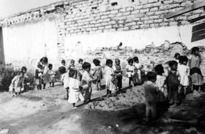 Niños regando el jardín en la escuela