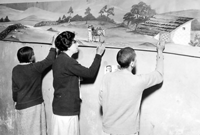 Maestra y alumnas pintando en mural