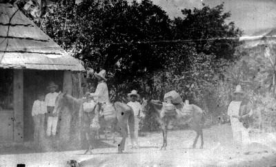 Aguadores con sus burros en patio de una casa rústica