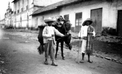 Indígenas con su asno en una calle