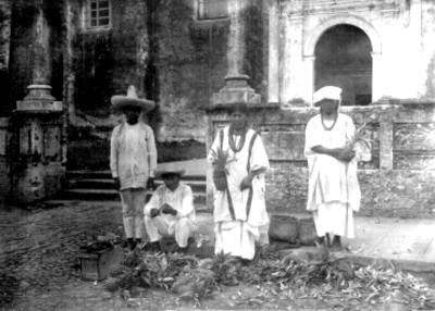 Dos hombres y dos mujeres totonacas vendiendo piñas fuera de una Iglesia, retrato