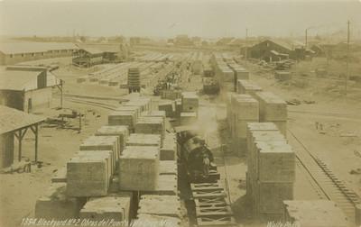Hombres descargan materiales en estación de ferrocarril