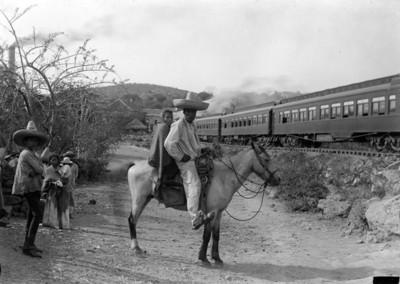 Pareja de hombre y mujer montados a caballo frente al ferrocarril