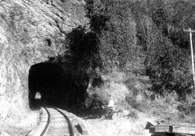 Hombre sentado a la entrada a un túnel ferroviario