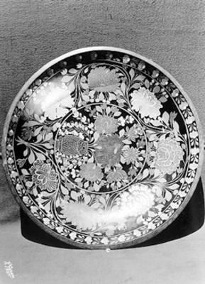 Plato decorado con flores blancas con un fondo negro vidriado, detalle