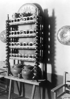 Vista parcial de ollas, tazones y un trastero fabricado con madera labrada