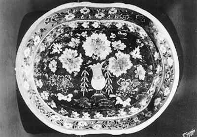 Platón de loza negra vidriada con motivos florales