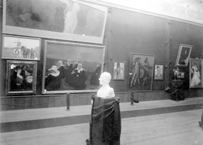 Sala de un museo con exposiciones de pinturas y esculturas, vista parcial