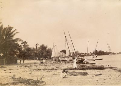 Mujeres, pescadores y embarcaciones en la playa