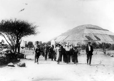 Grupo de personas caminan por la Calzada de los Muertos, al fondo la pirámide del Sol