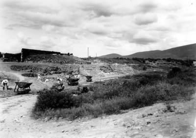 """""""Exploraciones - Primeros edificios"""", trabajadores llenan góndolas con tierra"""