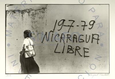 Mujer camina junto a muro con letrero político