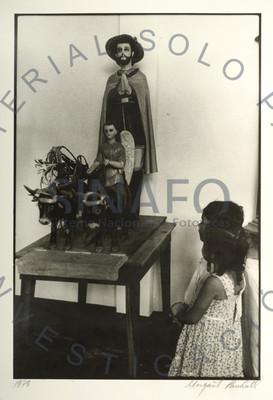 Dos niños frente a un santo sobre una mesa