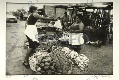 Vendedoras sonríen en un puesto de fruta en la calle