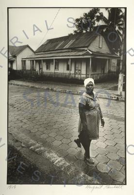 Mujer camina por una calle frente a casas de madera, retrato