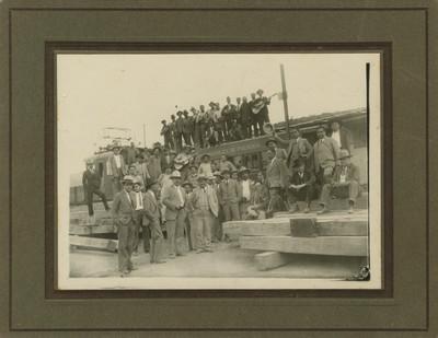 Grupo de hombres junto a vagón de ferrocarril