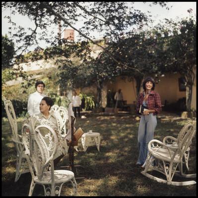 """Helena Rojo de pie ríe en jardín, escena de la película """"La Casa del Sur"""""""