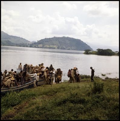 Hombres, mujeres y niños descienden de canoas a una isla, escena de la película La casa del sur