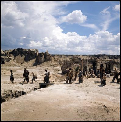 Hombres, niños y mujeres abandonan pueblo desértico, escena de la pelicula