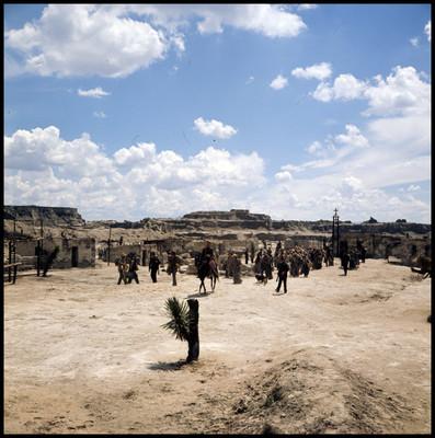 Soldado a caballo guía a personas en pueblo desértico, escena de la película la casa del Sur