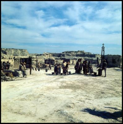 Hombres, mujeres y niños en fila con cubetas, escena de la película la casa del sur