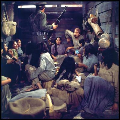 Soldado de pie con arma dentro de vagón con hombres y mujeres, escena de la película