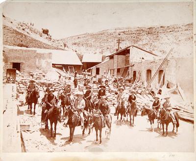 Hombres montados a caballo en el patio de una hacienda