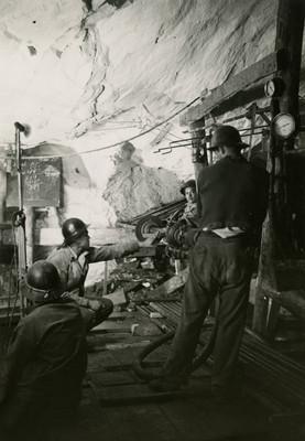 Mineros maniobran maquinaria dentro de un tunel