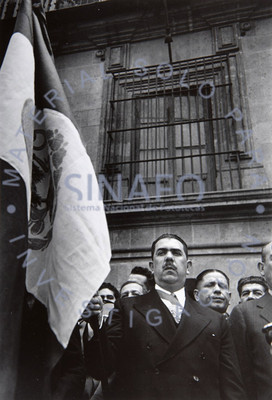 Lázaro Cárdenas sostiene la bandera de México en un acto público