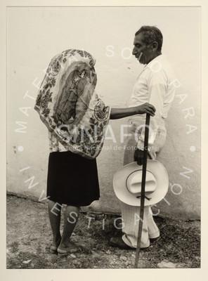 Hombre observa a mujer que sostiene un palo de madera