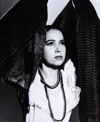 Zully Moreno, con vestuario teatral y brazos elevados cobijados con rebozo, fondo oscuro, retrato
