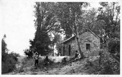 Personas sentadas al exterior de casa rústica, tarjeta postal
