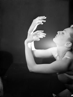 Bailarina coloca manos frente a su rostro de perfil, fondo oscuro con haz de luz