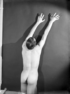 Bailarín desnudo de espaldas y arrodillado con manos elevadas sobre el muro