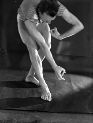Bailarín en posición dancística flexiona piernas y curva espalda
