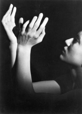 Bailarina eleva las manos, rostro de perfil izquierdo
