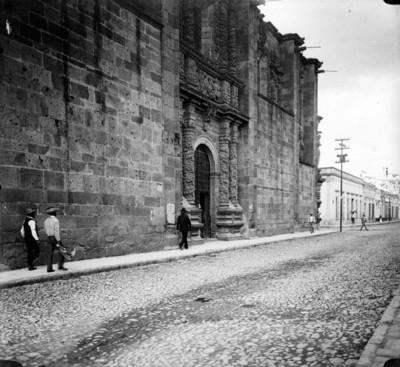 Gente camina por la calle frente a una iglesia