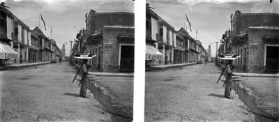 Vendedor ambulante con charola sobre la cabeza en una calle junto a una zanja con agua