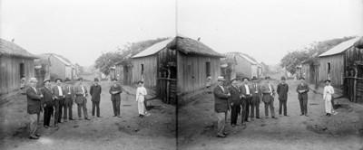 Grupo de hombres posan para retrato en una calle de poblado